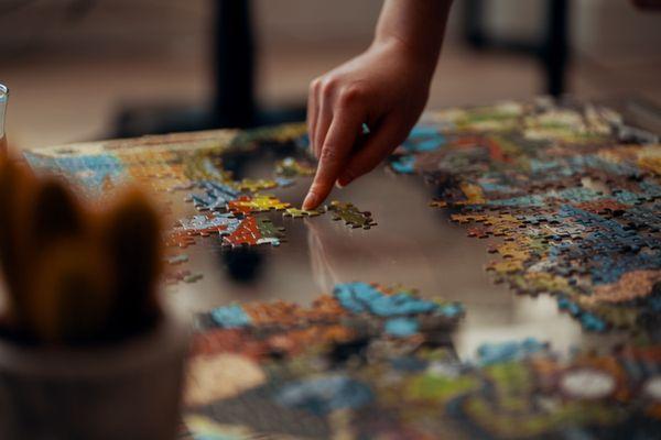 Une pièce d'un puzzle ajoutée par une main féminine sur une table