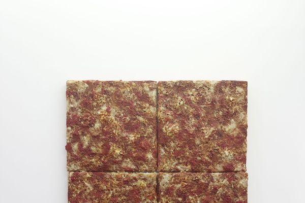 """Comme pour ses autres œuvres, Michel Blazy a souhaité donner une apparence et une odeur à son tableau """"Marguerite"""". Il a utilisé des colorants et arômes artificiels issus de l'industrie agro-alimentaire pour se rapprocher de la réelle odeur de la pizza."""