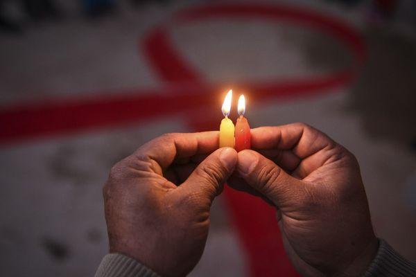 Une personne tenant deux bougies en hommage aux victimes du sida.