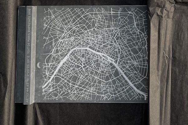 Un morceau recyclé de zinc provenant des toits de Paris. Ce modèle se tient debout seul et n'a pas besoin de support grâce à son pliage qui fait référence à la technique de couverture à tasseau traditionnelle des couvreurs.