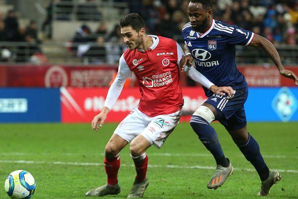 Le milieu de terrain Xavier Chavalerin de Reims (à gauche) dispute le ballon à l'avant centre de l'OL Moussa Dembele samedi soir au Stade de Reims.
