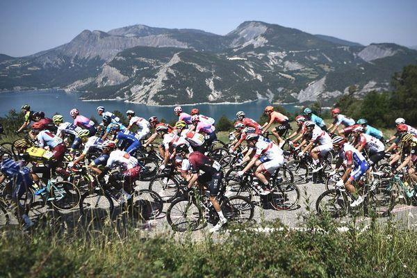 Le peloton passe près du lac de Serre-Poncon lors de la18e étape du Tour de France entre Embrun et Valloire, le 25 juillet 2019
