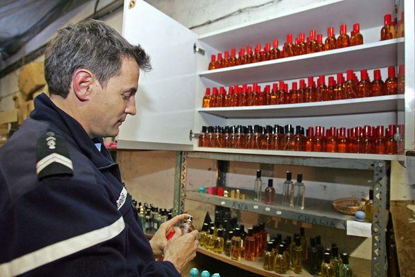 (Archives 2006). Un gendarme de la brigade de recherche d'Hyères (Var) fouille un laboratoire clandestin de fabrication de faux parfums de grandes marques.