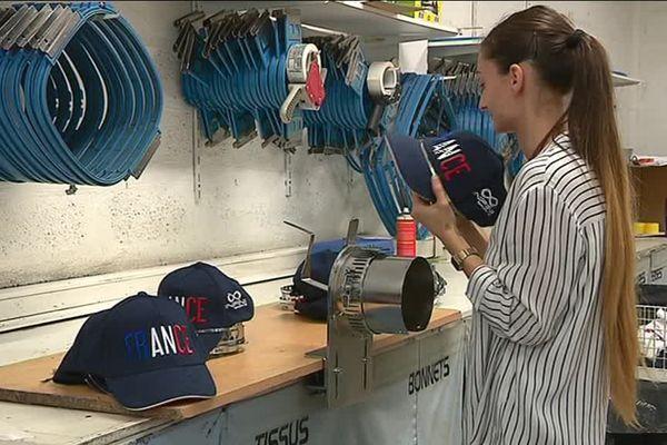 Une employée fabrique les casquettes.