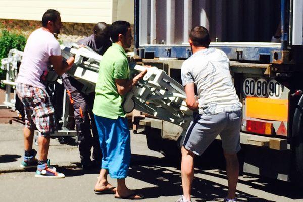 Les bénévoles chargent des lits médicalisés dans le container