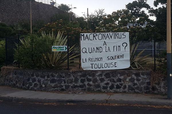 """Les banderoles fleurissent jusque sur l'île de la Réunion, en soutien à la jeune femme placée en garde à vue à Toulouse pour avoir afficher """"Macronavirus, à quand la fin ?"""" sur sa maison."""