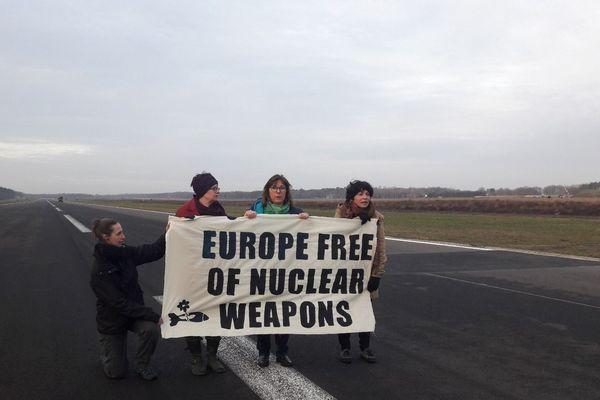 """Michèle RIvasi et les activistes d' """"Agir pour la paix"""" ont franchi les grillages et les barbelés avec une échelle avant d'être arrêtés par la police sur la piste d'envol de la base militaire belge."""