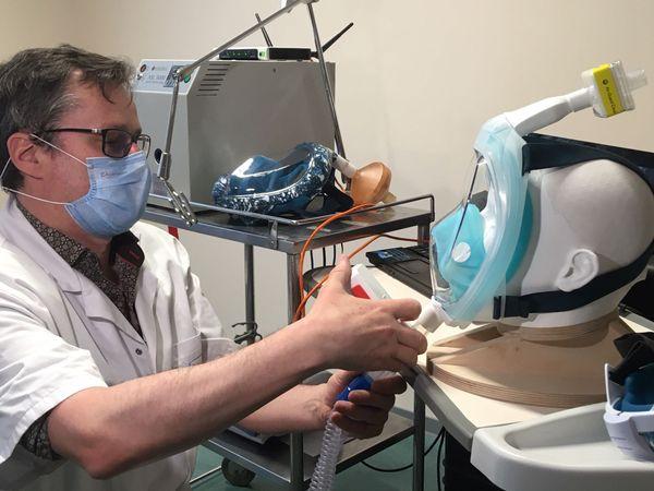 Le professeur Erwan L'Her essaie des masques et teste embouts et filtres sur le banc installé dans son bureau