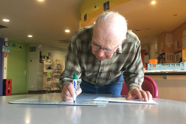 Michel, malade d'Alzheimer, écrit le menu du jour  pour conserver ses capacités restantes d'écriture.