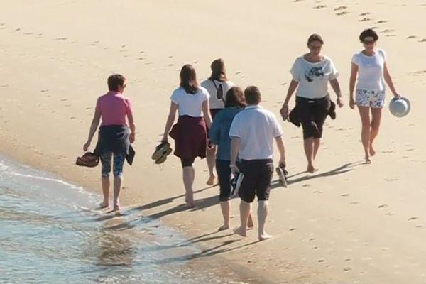 Pas encore de baignade mais une balade les pieds dans l'eau pour ces promeneurs sur une plage d'Arcachon.