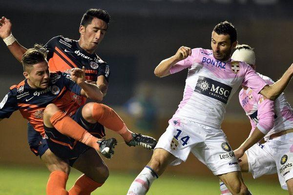 Les footballeurs Montpellierains Anthony Mounier (à gauche) et l'argentin Lucas Barrios (centre) à la lutte pour le ballon contre le milieu de terrain d'Evian Cedric Barbosa