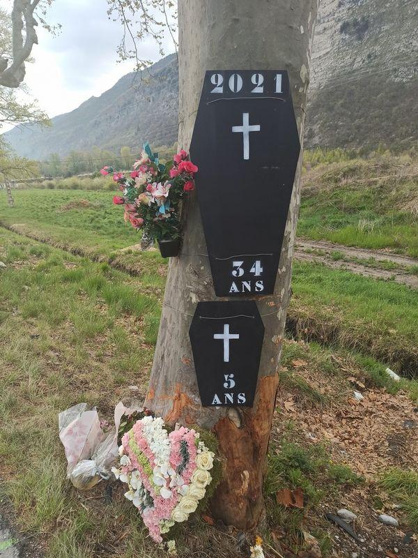 Des fleurs déposées devant les cercueils symboliques d'une mère et de sa fille qui ont perdu la vie sur cette route.