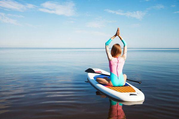 Parmi les activités à pratiquer cet été, testez le paddle yoga en piscine ou sur l'océan
