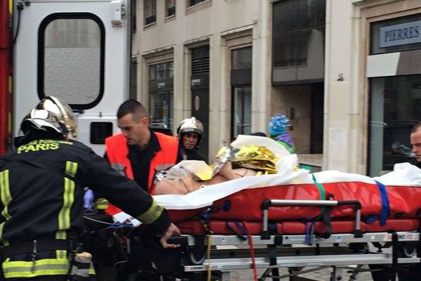 """Paris : Firefighters carry an injured man on a stretcher in front of the offices of the French satirical newspaper Charlie Hebdo in Paris on January 7, 2015, after armed gunmen stormed the offices leaving at least one dead according to a police source and """"six seriously injured"""" police officers according to City Hall."""