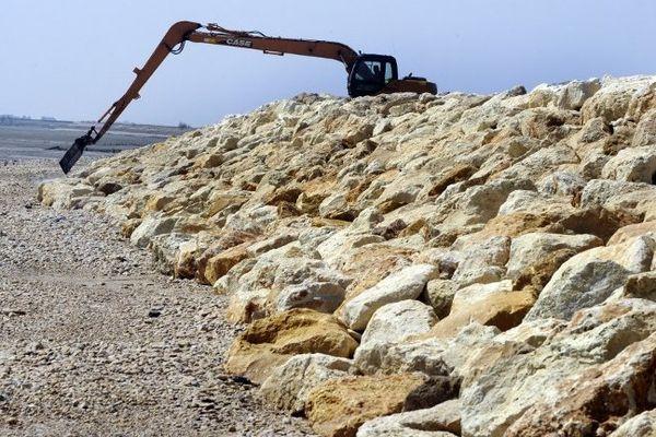 Un tractopelle renforce la digue de protection sur la commune de Loix, sur l'île de Ré, aprés le passage de la tempête Xynthia.