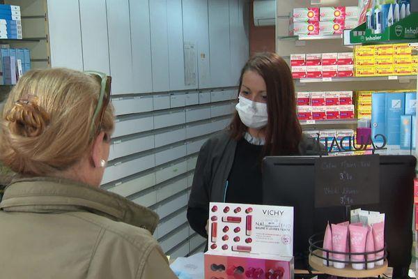 Une préparatrice équipée d'un masque sert une cliente dans une pharmacie des Alpes-Maritimes.
