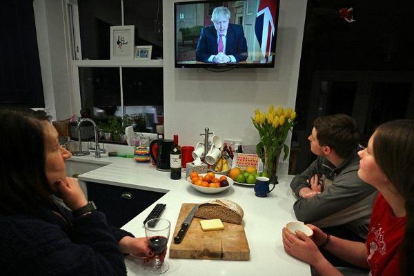 Une famille de Liverpool écoutant ce lundi soir le Premier ministre Boris Johnson à la télévision.