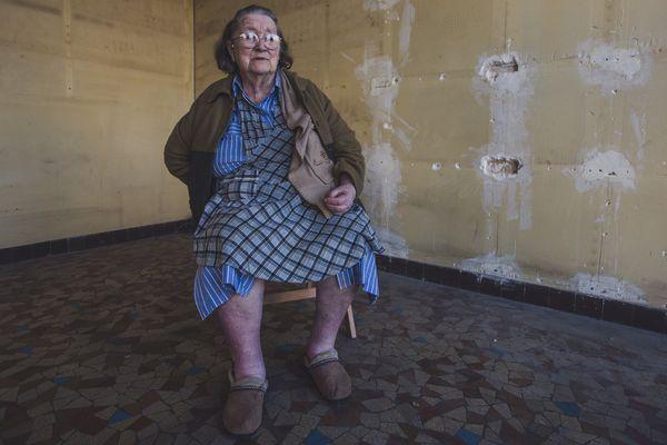 """Marguerite pose une dernière fois dans sa boutique vide. A 89 ans, """"il est temps de faire une pause"""". Mais elle ferme son magasin à contre-coeur."""