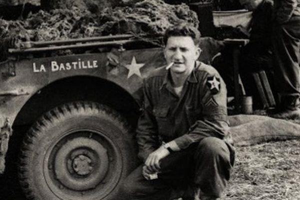 """Bernard Dargols en 1944, en Normandie. Il pose devant sa jeep """"La bastille"""""""