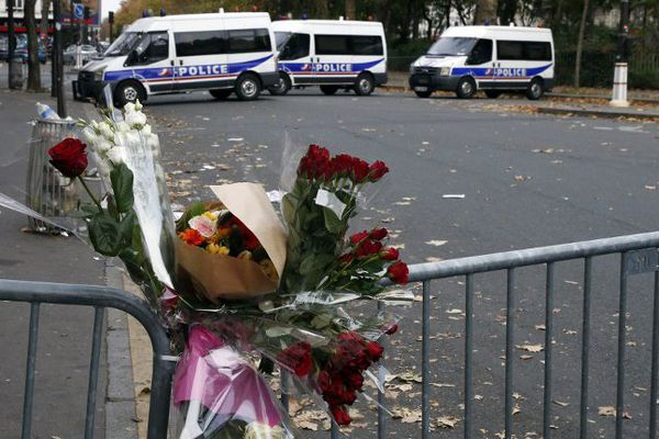 Des bouquets accrochés à la grille devant le Bataclan à Paris, le 14 novembre 2015.