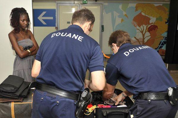 """Deux agents des douanes fouillent des bagages à l'aéroport d'Orly, en marge du lancement de la campagne """"voyageurs"""", informant les vacanciers de leurs droits et obligations."""