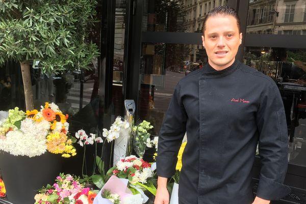 Axel Manès perpétue la cuisine de Joël Robuchon dans le restaurant L'Atelier Joël Robuchon Saint-Germain. Des personnes ont déposé spontanément des fleurs devant le restaurant.
