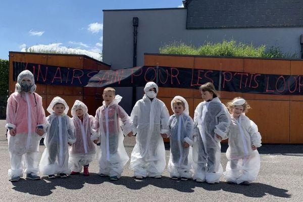 Masques et combinaisons blanches, les enfants prennent la pose devant l'école d'Anor. Une action menée par les parents pour alerter sur l'épandage des pesticides près des écoles.