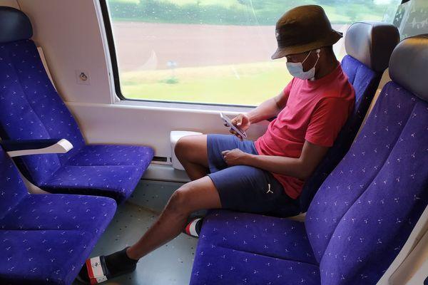 Dans le Train, Said passe le temps en regardant des vidéos sur son téléphone.