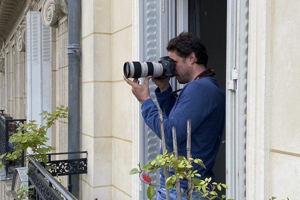 Un photographe à sa fenêtre à Paris.