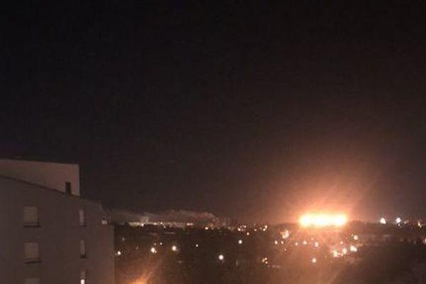 Le panache de fumée se dégageant de l'incendie était visible de loin. (à gauche des éclairages oranges circulaires)