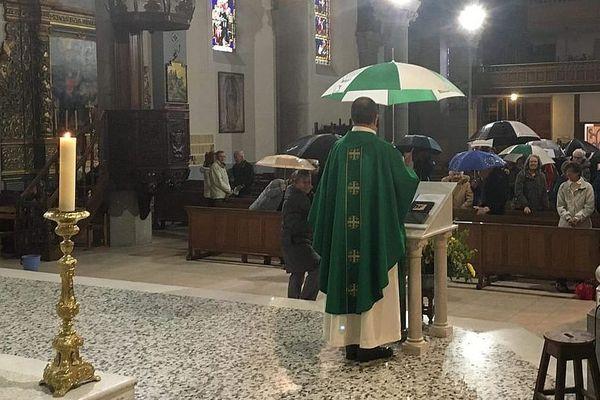 03/11/2019 - A Barcelonnette,les fidèles et le curé de la paroisse célèbrent la messe sous des parapluies pour obtenir des travaux de la mairie.
