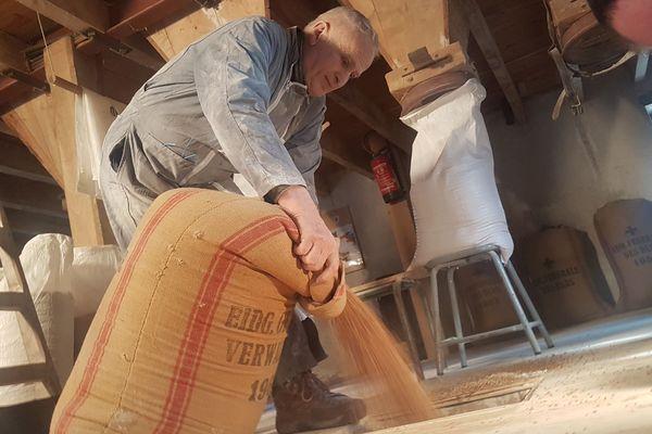 Sac après sac, Jean-Claude verse lui-même son blé au-dessus des meules.