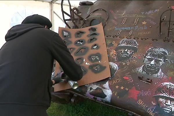 L'artiste Jeff Aérosol utilise des pochoirs pour figer les visages de victime sur un char de la Seconde Guerre Mondiale.