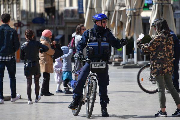 Place de la Comédie à Montpellier, la police municipale contrôle les attestations des passants, le 25 mars.