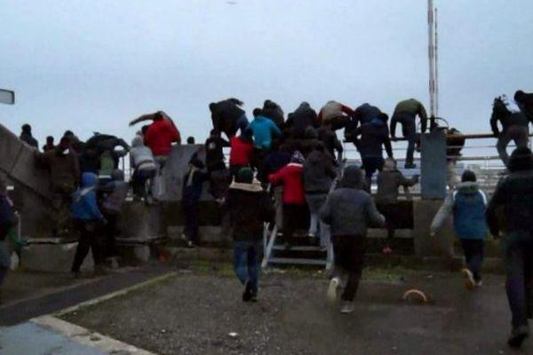 Des migrants s'introduisant dans le port de Calais, le 23 janvier 2016, en marge d'une manifestation.
