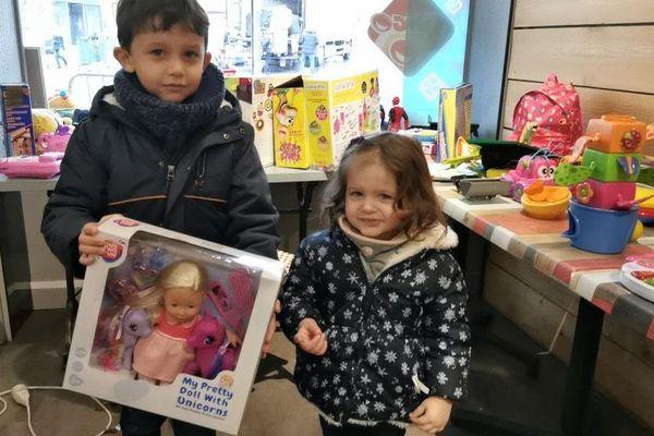Ethan, 6 ans, et sa petite soeur Ambre, 3 ans, distribuent les jouets récoltés aux familles dans le besoin.