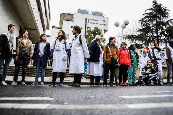 Des centaines de personnes ont formé une chaîne humaine autour de l'hôpital Robert Debré (Paris XIXe) pour défendre l'hôpital public.