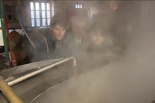 Un  jeune brasseur belge et un brasseur du Tarn travaillent ensemble au brassage d'une nouvelle bière.