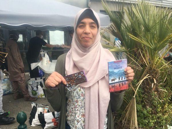 Leila ravie d'avoir récupéré deux masques et quelques livres distribués gratuitement.