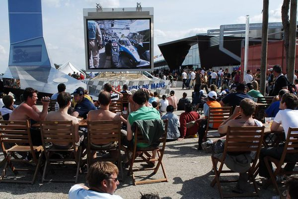 Dans le village des 24 Heures du Mans, des spectateurs regardent l'écran géant qui retransmet la course.