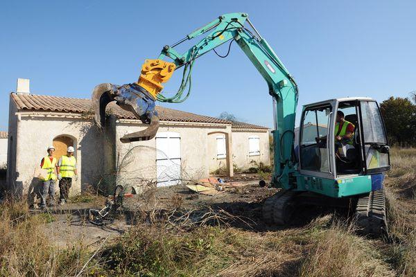 En octobre 2011, une pelleteuse s'apprête à détruire une maison située en zone noire