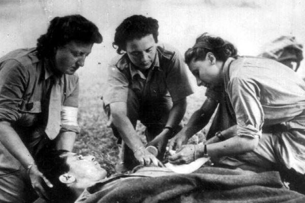 Trois Rochambelles de la Division Leclerc soignent un blessé sur un brancard.