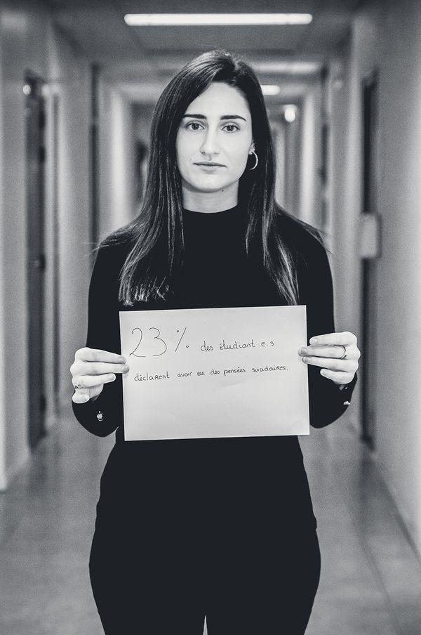 """Une étudiante porte une pancarte avec un message : """"23% des étudiant.e.s déclarent avoir des pensées suicidaires"""""""
