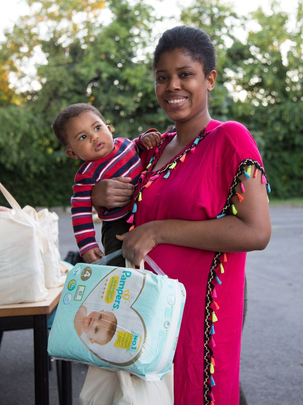 Une maman reçoit un colis pour son bébé lors d'une distribution de l'association MaMaMa