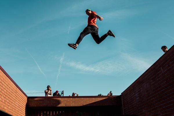 Un homme pratiquant l'Art du déplacement, s'élançant d'un mur à un autre.