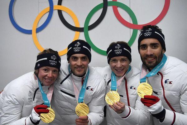 Les médaillés d'or du biathlon français Marie Dorin Habert, Simon Desthieux, Anaïs Bescond et Martin Fourcade posent devant les anneaux olympiques lors des Jeux olympiques d'hiver 2018 de Pyeongchang, le 21 février 2018.