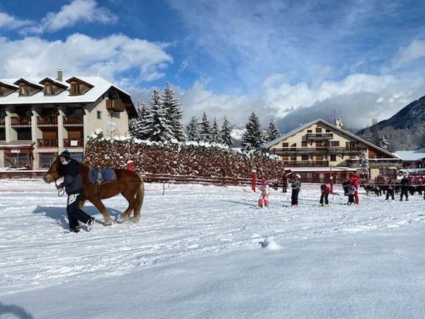 Les enfants de l'ESF tractés par un cheval à Saint-Léger-les-Mélèzes.