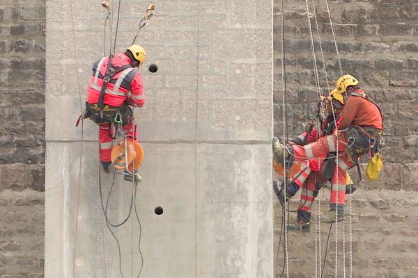Sur le barrage de Chazilly des techniciens-cordistes gravent le béton de la nouvelle tour de vidange centrale afin d'imiter les moellons de grès du parement d'origine.