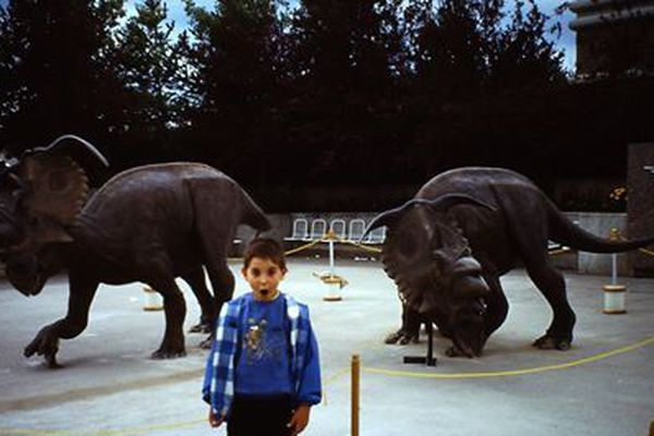 Jonathan Brunn, enfant, pose devant les dinosaures du Musée royal d'Alberta au Canada.
