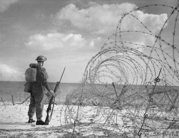 Un soldat britannique, le 7 octobre 1940, sur une plage du sud de l'Angleterre, protégée par des barbelés.
